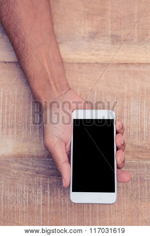 Directly above shot of man holding on phone with black screen over table