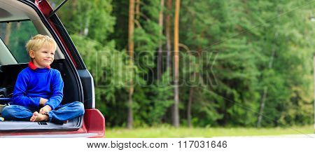 happy little boy travel by car in summer nature