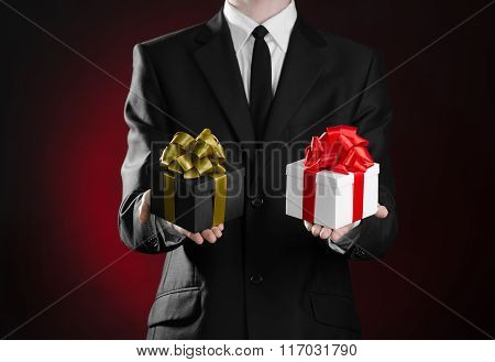 Theme Holidays And Gifts: A Man In A Black Suit Holding Two Exclusive Gift Packaged In A Black Box W