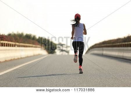 young fitness woman runner running on city road
