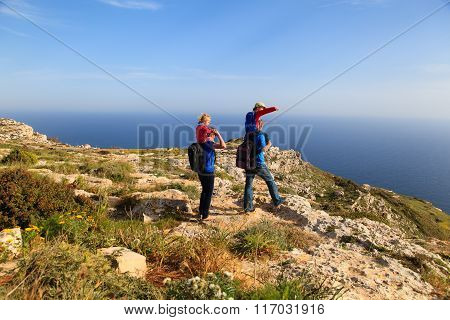 family with two kids on shoulders hiking in mountains