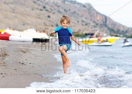 little blond kid boy running ocean beach