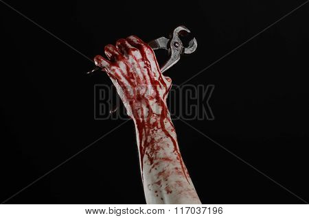 Halloween Theme: Bloody Hand Holding A Pliers On A Black Background