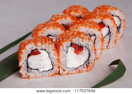 roll with tobiko orange, shrimp and sweet red peppers on a tropical leaf close-up menu isolated