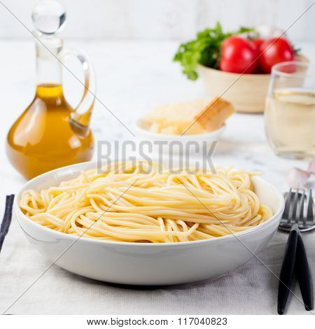 Cooked spaghetti pasta in plate on grey napkin Pasta ingredients on grey stone background