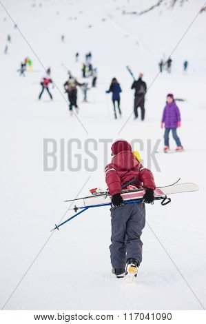 Boy with skis up the hill for skiing