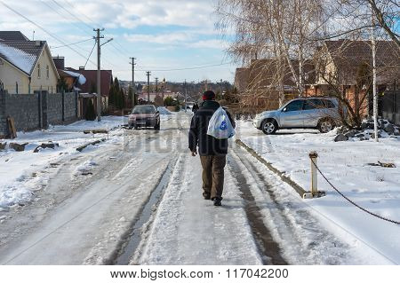 Man carrying purchases from a remote local shop walking on a snowy slippery street covered with melt