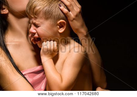 Portrait of a crying son on the mother's hands