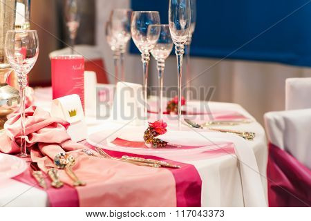Elegant table set in soft red and pink for wedding or event part