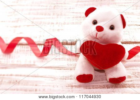 White Teddy Bear Holding A Red Heart On White Rustic Wooden Background. Valentine's Day And Mother's