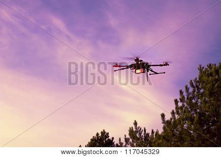 Dark Silhouette Of Drone Hovering In A Colorful Sunset. Toned Image. Soft Focus