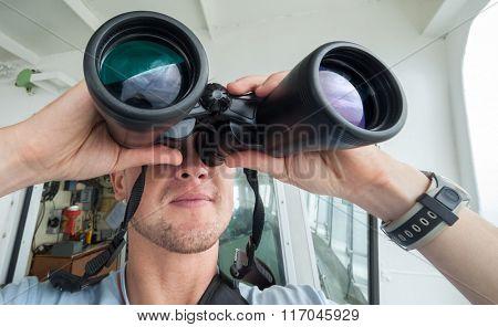 Man looks through binoculars from the boat