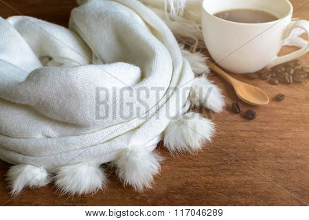 Scarf And Cup Of Coffee On Wooden Table