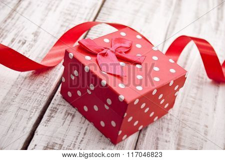 Red Gift Box With Ribbon On Rustic White Wooden Table. Valentine's Day And Mother's Day Background.