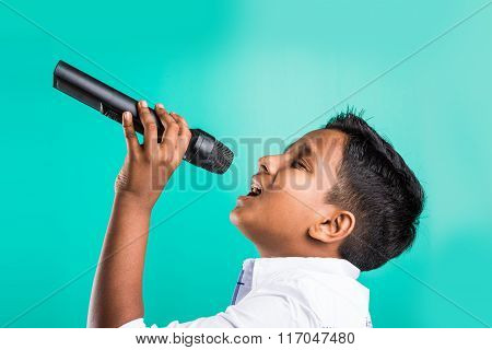 young indian boy in white shirt yelling in microphone, little kid singing, Little indian boy with mi
