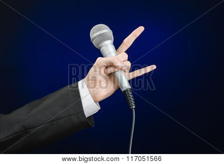 Business And Speech Topic: Man In Black Suit Holding A Microphone On A Gray Dark Blue Isolated Backg