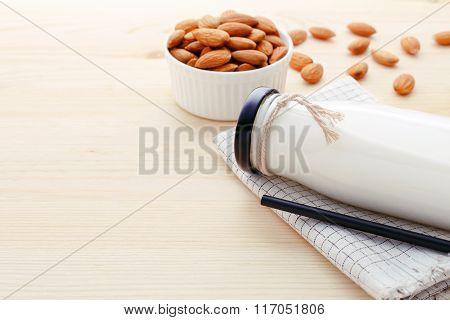 Almond Milk In Bottle On Wood Background