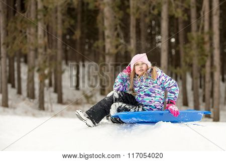 Confident Girl Sitting With Her Sled On A Hill