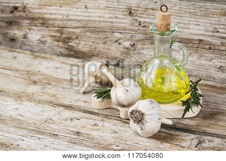 Simple kitchen still life with bottle of olive oil and garlic on a wooden cutting board. The concept of the family home healthy cooking. selective Focus