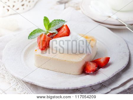 Pudding, cheesecake, custard dessert, with sour cream and fresh strawberry and mint leaves on a whit
