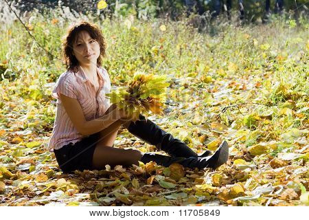 Girl With Maple Leaves In Park