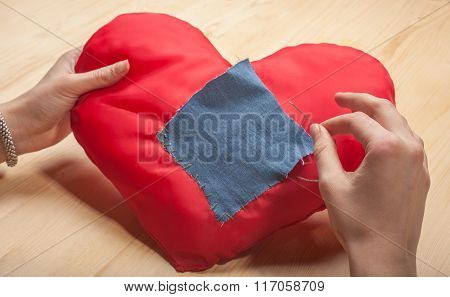 Female Hands Sew A Patch On The Heart