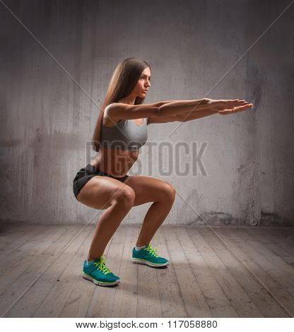 Attractive Sportswoman Doing Squats In Brutal Interior