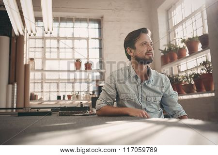 Small business owner looking away thoughfully in his studio