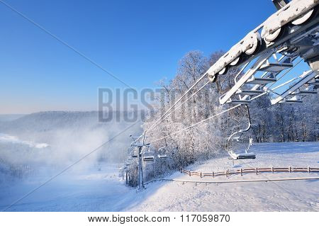 Chair Lift For Skiing Covered In Snow And Hoarfrost With A Skiing Slope View