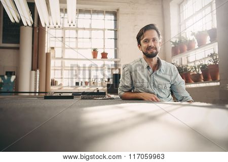 Positive small business owner sitting in his studio workshop