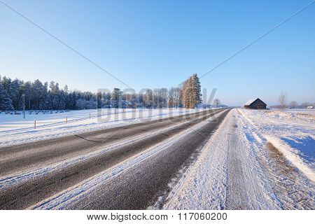 Winter Highway On A Sunny Day With Snowy Trees And A Rural Cottage