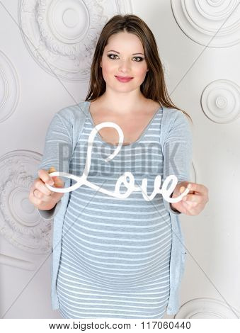 Beautiful pregnant woman with wooden world