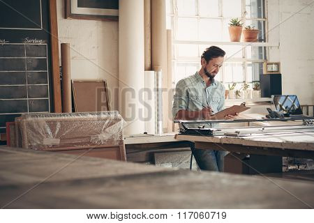 Entrepreneur in his workshop checking figures on a clipboard