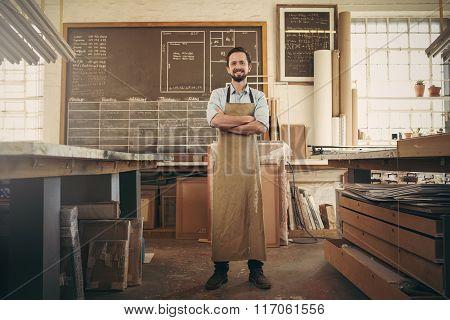 Confident craftsman standing in his workshop studio