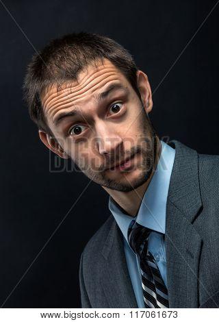 Surprised bearded businessman over dark background