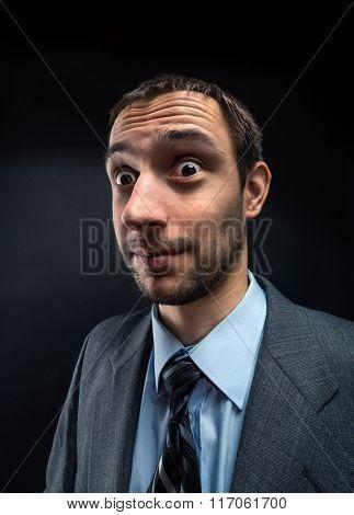 Portrait of nerd businessman over dark