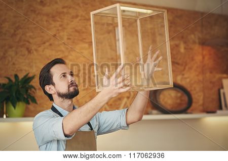 Confident craftsman holding up a project that he designed