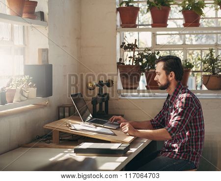 Designer working on laptop in his creative office space
