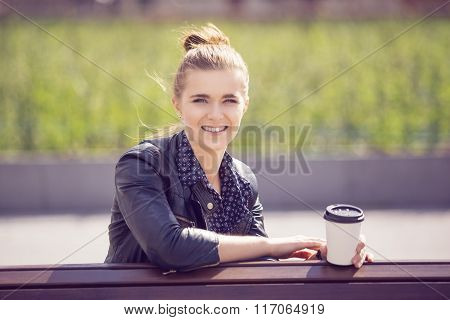 Attractive Young Woman Sitting On A Bench With Coffee