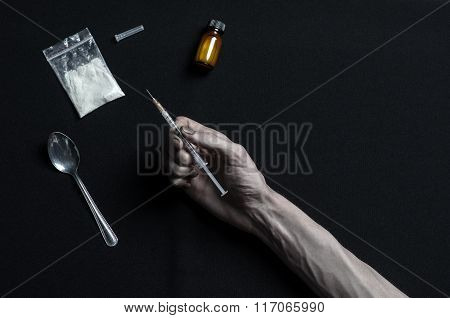 The Fight Against Drugs And Drug Addiction Topic: Hand Addict Lies On A Dark Table And Around It Are