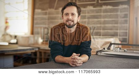 Positve young designer leaning on table in his studio