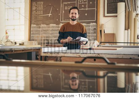 Professional craftsman checking orders and stock in his studio