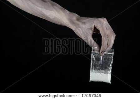The Fight Against Drugs And Drug Addiction Topic: Dirty Hand Holding A Bag Addict Cocaine On A Black