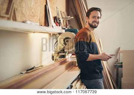 Young carpenter looking up while using phone in his workshop
