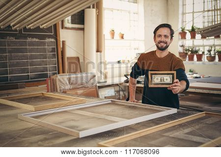Entrepreneur holding up a framed bank note in his workshop