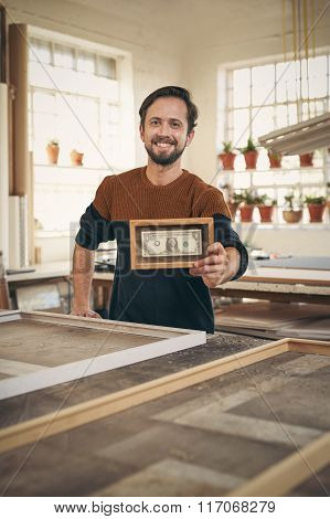 Craftsman in his studio holding up a framed bank note