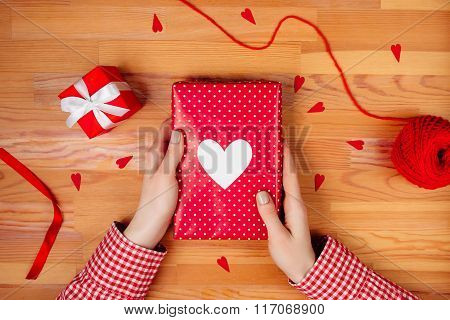 Female hands wrapping gift on wooden table