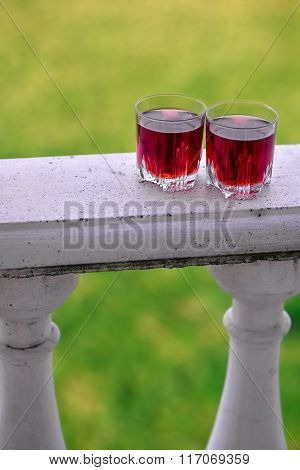 Two glasses with red drink on balcony rail