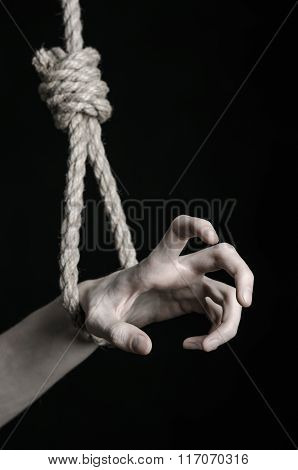 Suicide And Depression Topic: Human Hand Hanging On Rope Loop On A Black Background