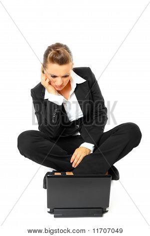 Sitting on floor bored modern business woman looking in laptop isolated on white